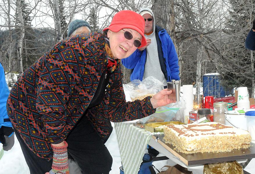 Katharine has something to warm up the birthday cake. Photo: Ian Webster, Merritt Herald